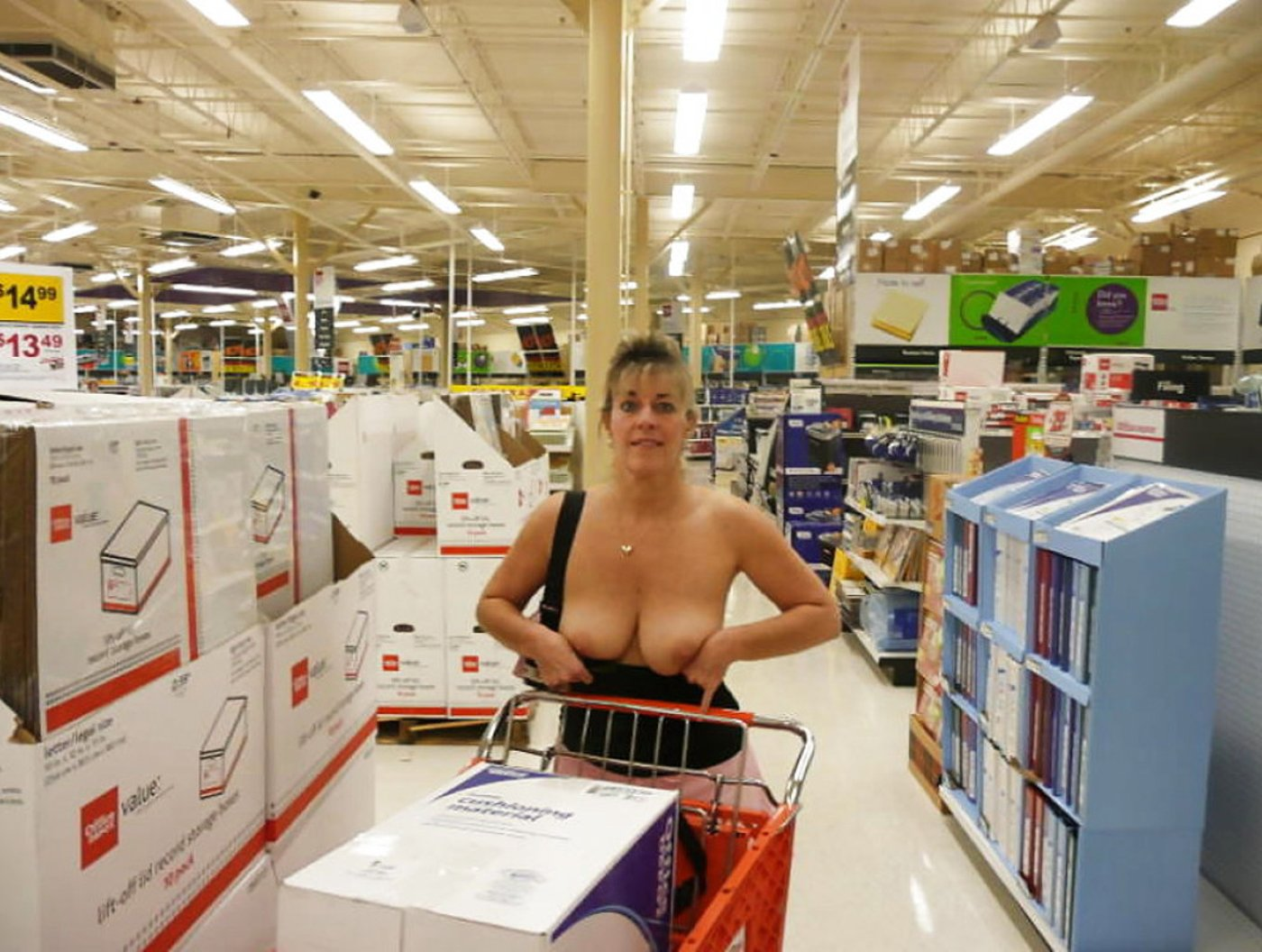 Mature lady showing her boobs and posing topless inside a shop