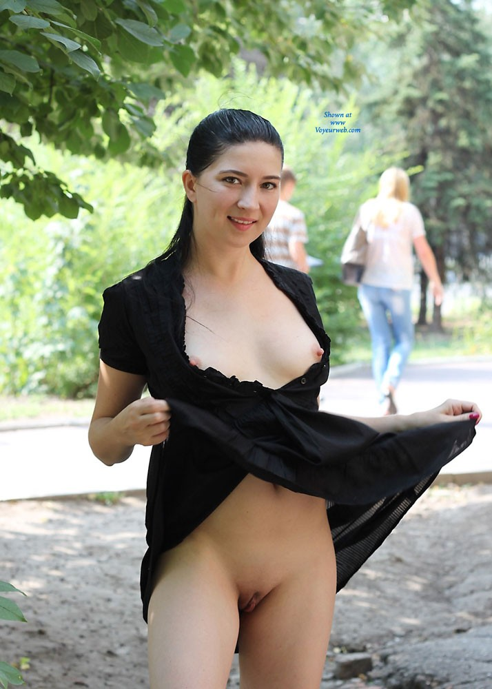 Almost nude in a park in a short open dress and showing her boobs and shaved pussy