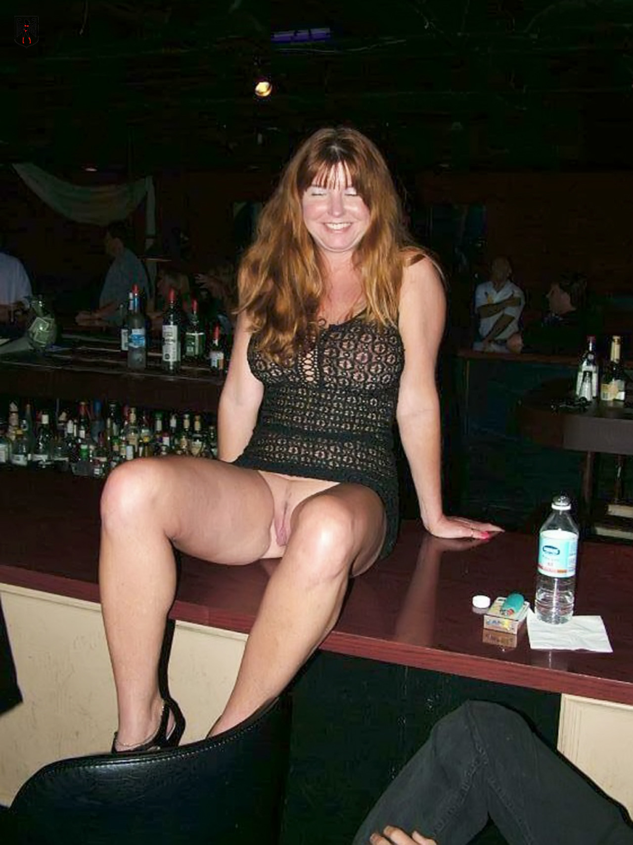 Milf sitting on a bar table in a short dress and showing her bottomless pussy