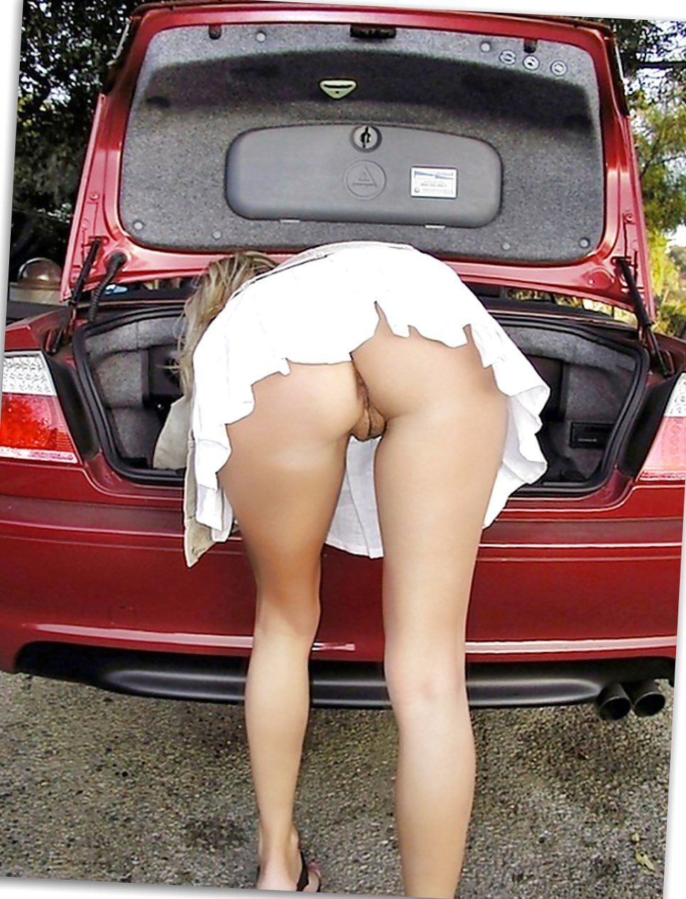 Bending in a short skirt while loading in a car boot and flashing her pussy and legs
