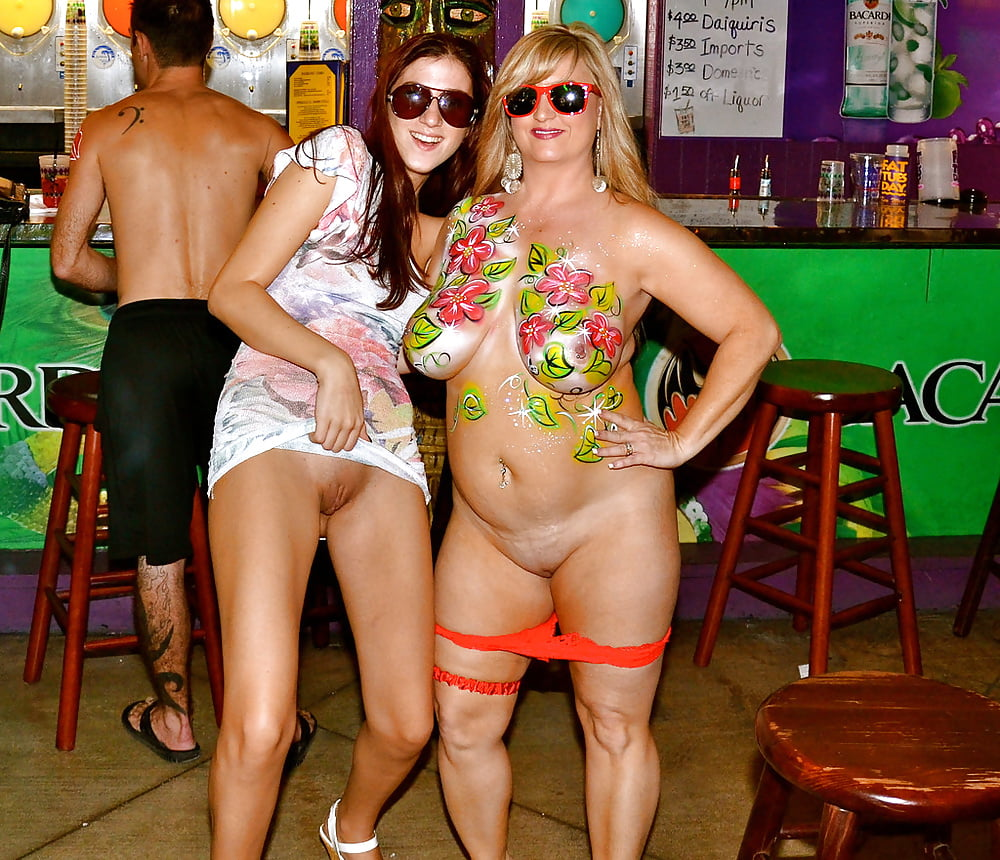Almost nude milf in body paint exposing her big boobs and showing her pussy along with her friend
