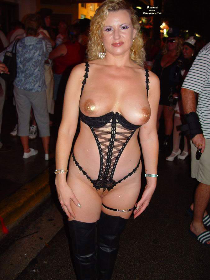 Almost nude milf in a threadbare corset type dress and showing her big boobs and pussy