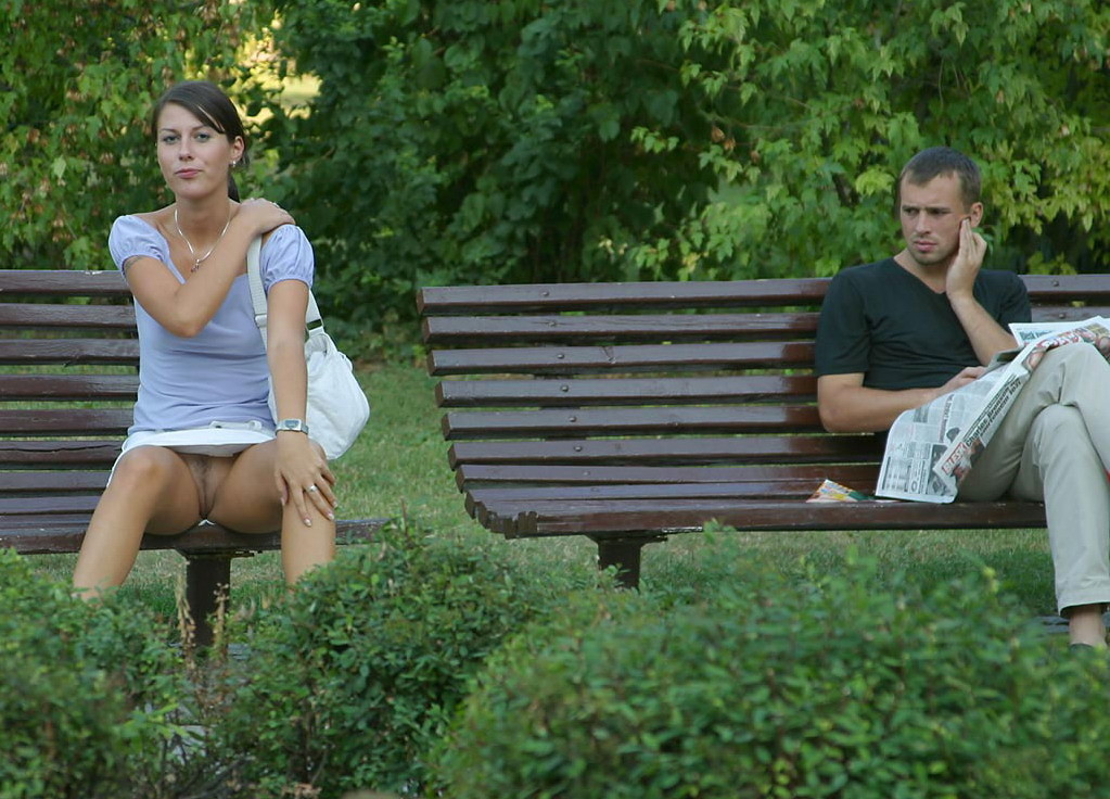 Sitting on a park bench near a stranger and exposing her landing strip pussy in a short skirt