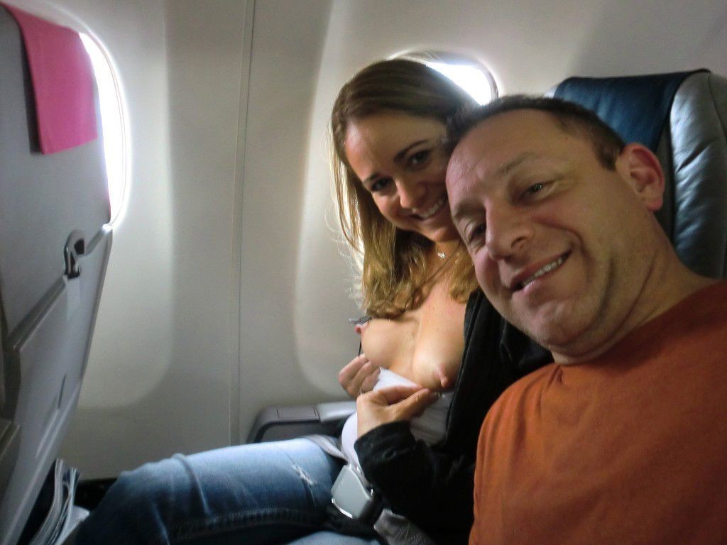 Flashing her boobs and nipples and posing almost topless inside an airplane